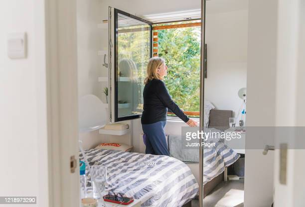 senior woman standing by bedroom window - open stock pictures, royalty-free photos & images