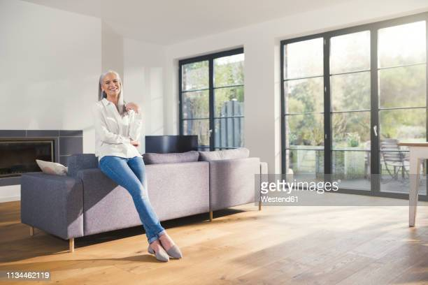 senior woman standing by couch in living room - one senior woman only stock pictures, royalty-free photos & images