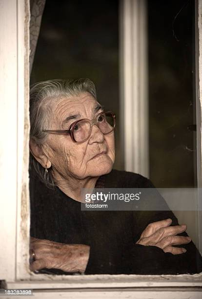 Senior woman standing by the window and looking out