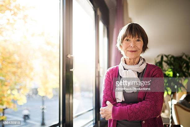 Senior Woman Standing By Window