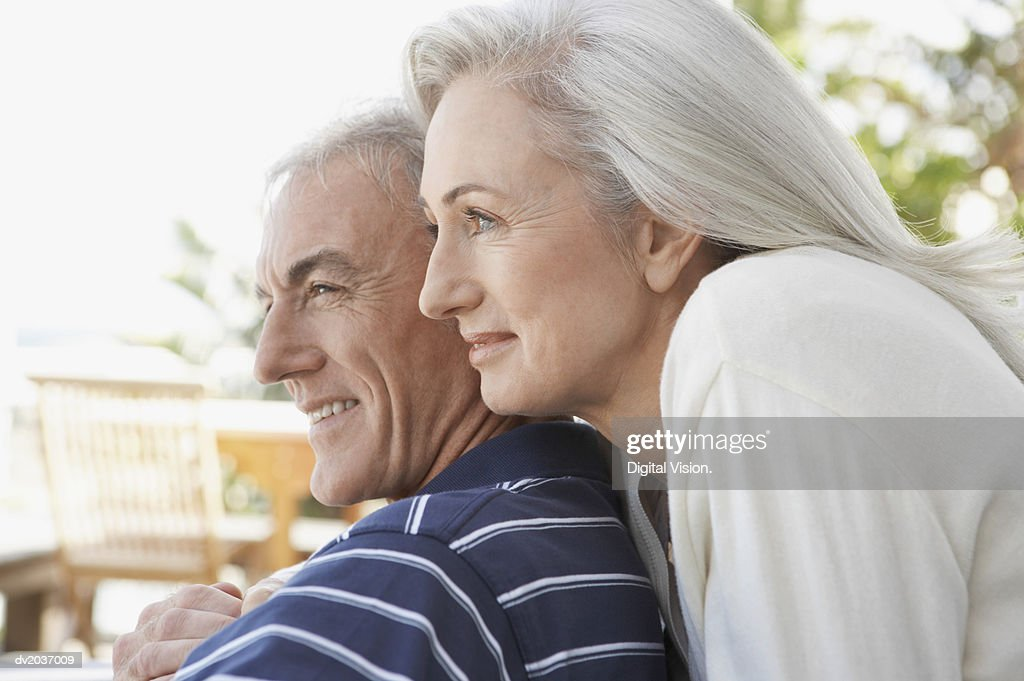Senior Woman Standing Closely Behind a Senior Man : Stock Photo