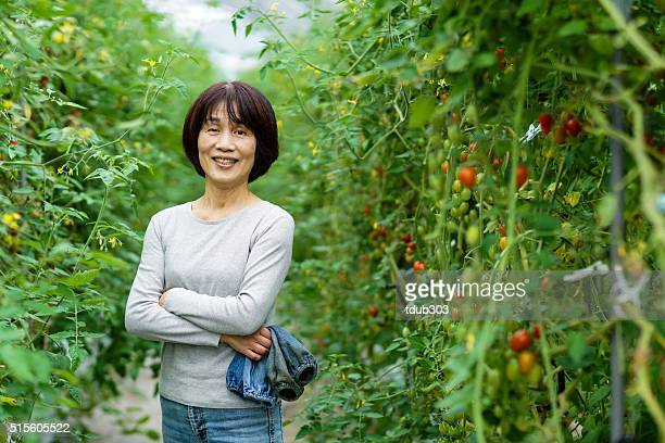 Senior woman standing confidently in her small business greenhouse