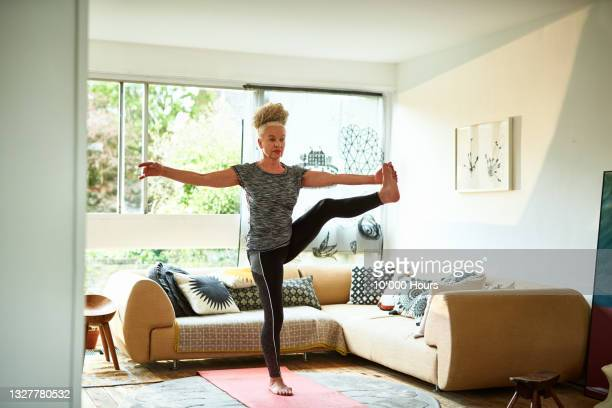 senior woman standing in balance yoga pose - greater london stock pictures, royalty-free photos & images