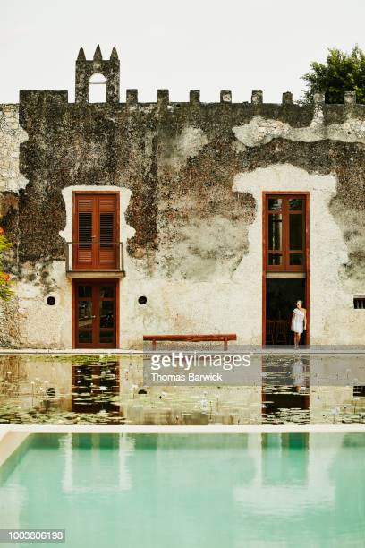Senior woman standing in doorway at luxury resort looking out