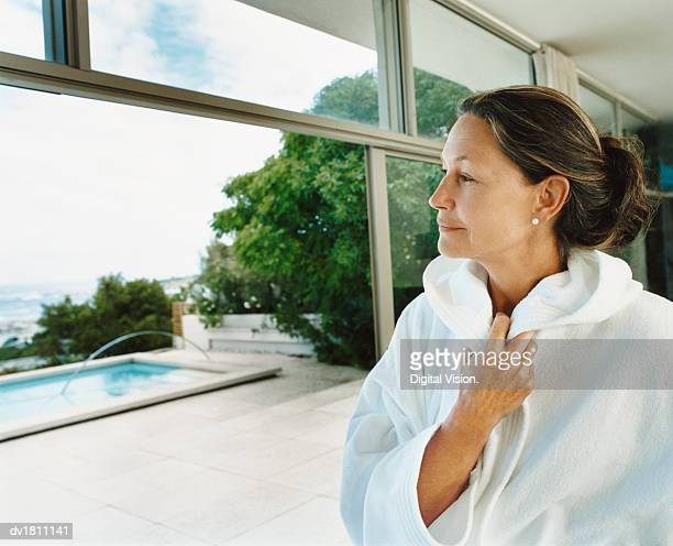 Senior Woman Standing in Her Home Dressed in a White Robe Looking Out Onto a Coastal Garden