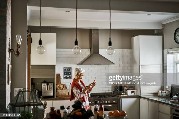senior woman standing in her kitchen and sending a text on her cellphone - part of a series stock pictures, royalty-free photos & images