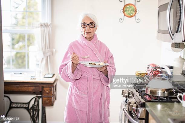 senior woman standing in kitchen holding plate of food - bathrobe stock pictures, royalty-free photos & images