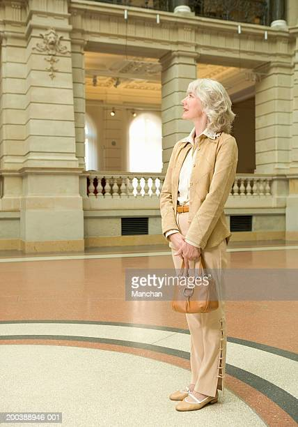 senior woman standing in museum concourse, holding handbag - beige purse stock pictures, royalty-free photos & images
