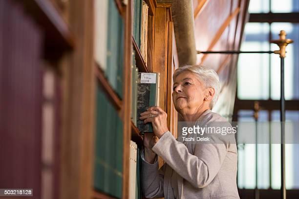 Senior Woman Standing Next To The Bookshelves