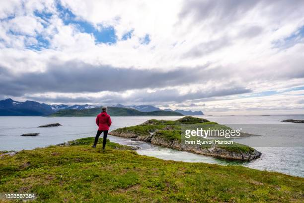 senior woman standing on a mountain covered in grass - looking out over the ocean - finn bjurvoll stock pictures, royalty-free photos & images