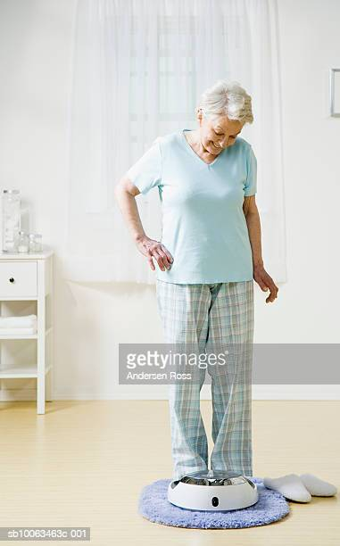 Senior woman standing on bathroom scale at home