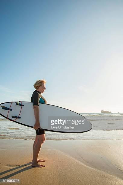 senior woman standing on beach with surfboard, camaret-sur-mer, brittany, france - camaret sur mer photos et images de collection
