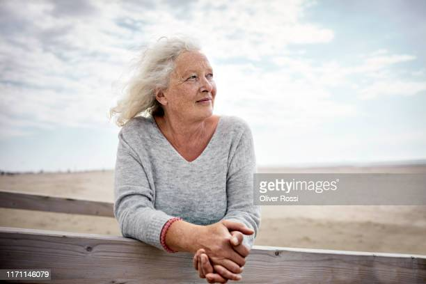 senior woman standing on boardwalk on the beach - senior women stock pictures, royalty-free photos & images