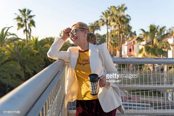 Senior woman standing on bridge, enjoying the sunshine, holding reuseable cup