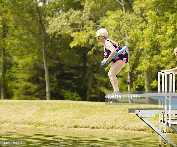 Senior woman standing on diving board, side view