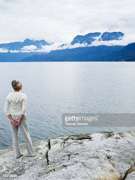 Senior woman standing on rocks looking at view