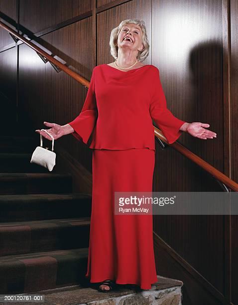 高齢者の女性の上に立つ階段、腕を広げる、笑顔 - イブニングウェア ストックフォトと画像