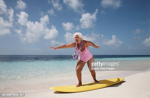 senior woman standing on surfboard - old woman in swimsuit stock pictures, royalty-free photos & images