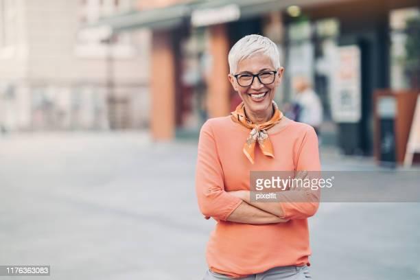 都会の屋外に立つシニア女性 - マフラー ストックフォトと画像