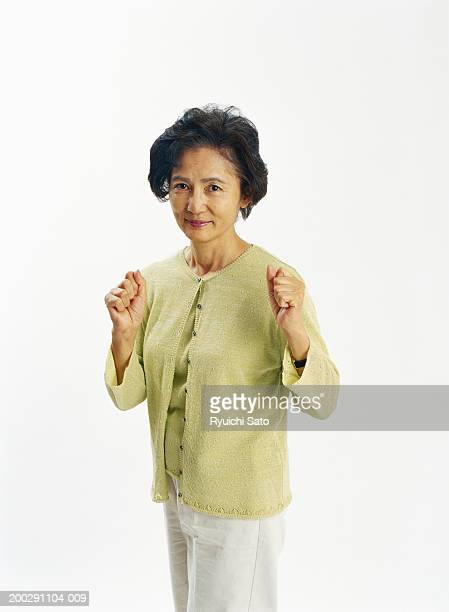 Senior woman standing, punching the air, portrait