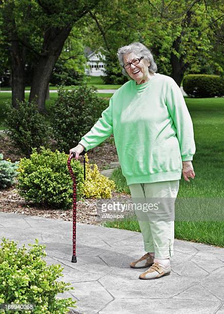 senior woman standing with cane - fat old lady stock photos and pictures