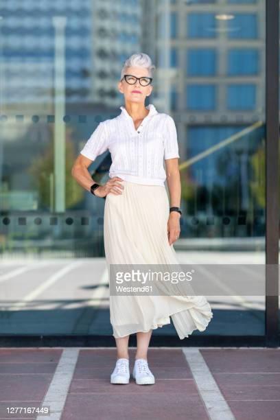 senior woman standing with hand on hip against glass window in city - só uma mulher idosa imagens e fotografias de stock