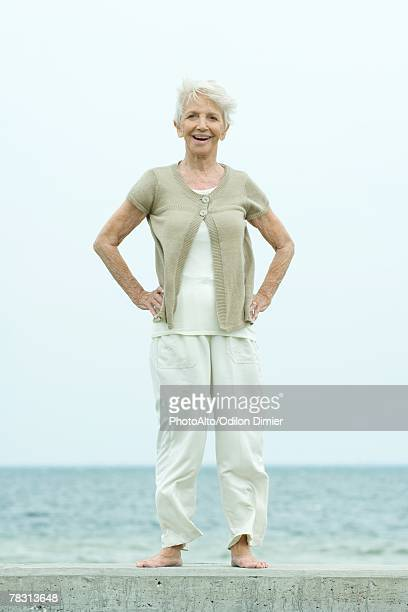 Senior woman standing with hands on hips, smiling at camera, ocean in background, full length