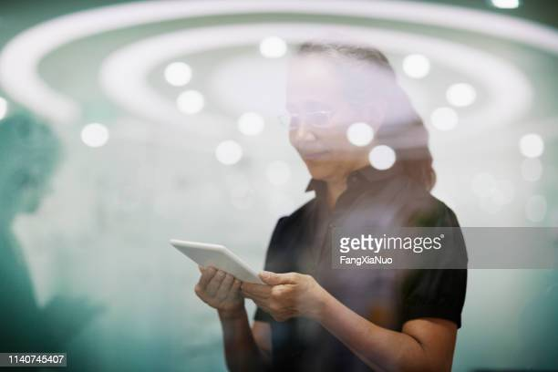 senior woman standing with smart tablet computer - angel halo stock pictures, royalty-free photos & images