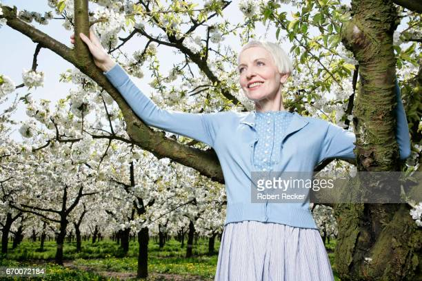 senior woman stands between blossoming cherry trees - vitalität stock pictures, royalty-free photos & images