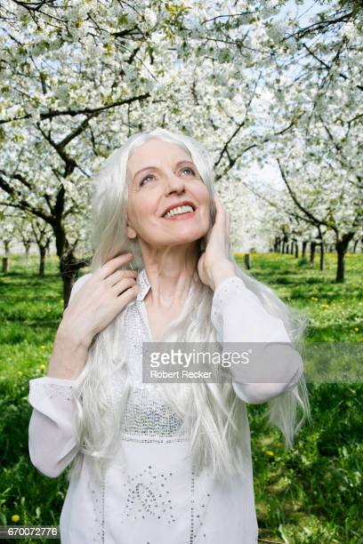 senior woman stands between blossoming cherry trees - gutaussehend stock pictures, royalty-free photos & images