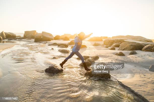 senior woman stepping across stream on the beach at sunset - fortschritt stock-fotos und bilder