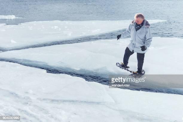 Pasos de mujer Senior en témpanos de hielo en el lago Superior