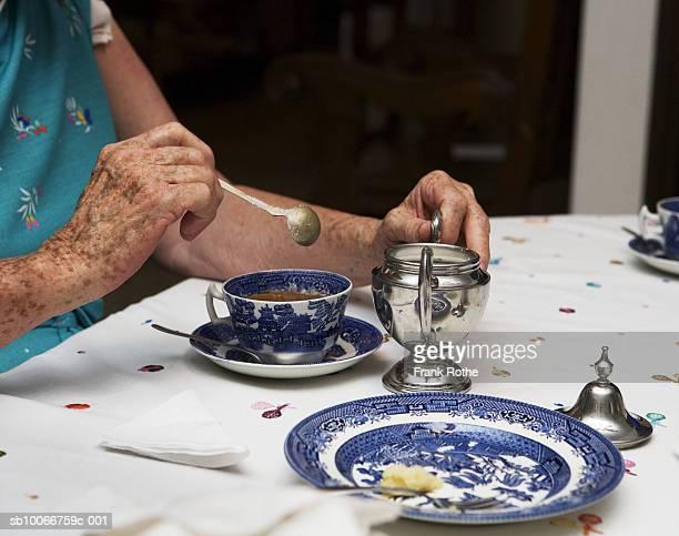 senior woman stirring afternoon tea at table, mid section - santa cruz de la sierra bolivia fotografías e imágenes de stock