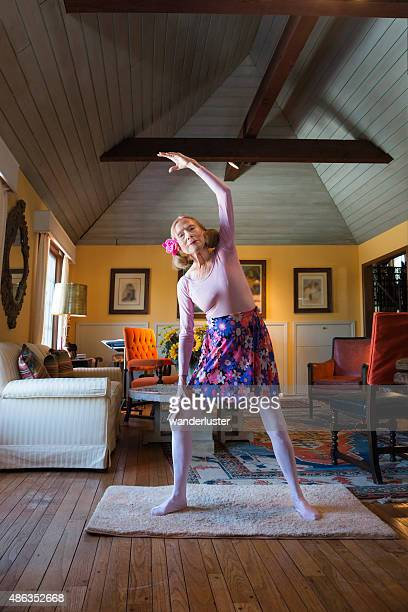 Senior woman stretches in her home