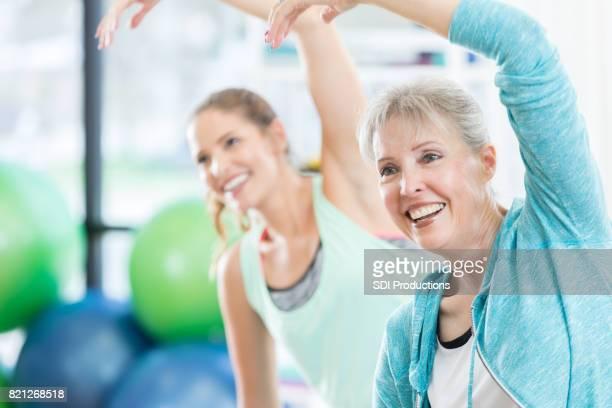 Senior mujer estira el torso durante la clase de ejercicio en el gimnasio
