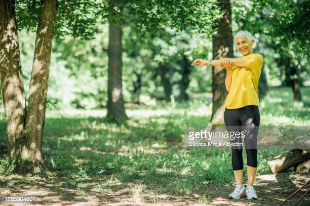 senior woman stretching after a outdoor walking exercise - beautiful people stock pictures, royalty-free photos & images