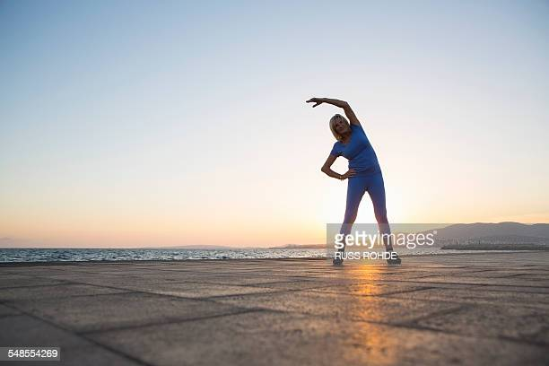 senior woman stretching by beach - old women in pantyhose stock photos and pictures