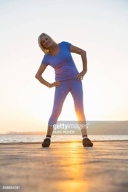senior woman stretching by beach - old women in pantyhose stock pictures, royalty-free photos & images