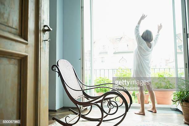 senior woman stretching her body near window - nachthemd stockfoto's en -beelden