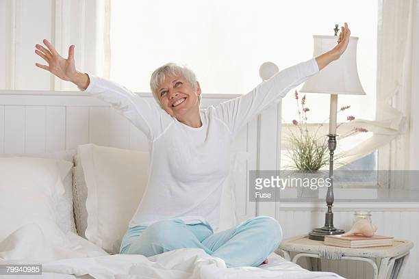 senior woman stretching in bed - white hair stock photos and pictures