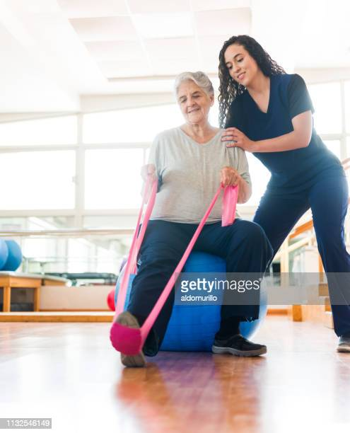 senior woman stretching leg with exercise band - cute nurses stock pictures, royalty-free photos & images