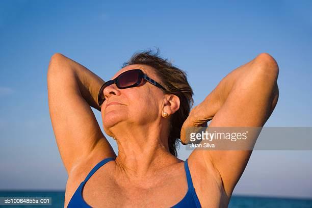 Senior woman stretching on beach, close-up