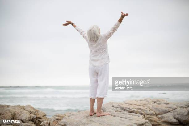 senior woman stretching on beach - aging process stock pictures, royalty-free photos & images