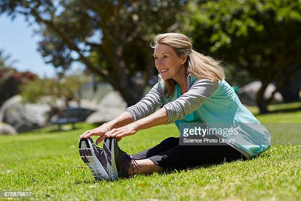 senior woman stretching on grass - old lady feet stock pictures, royalty-free photos & images