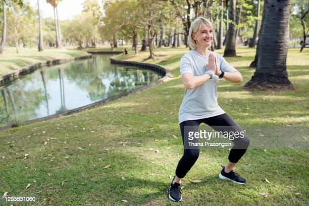 senior woman stretching - aktiver lebensstil stock-fotos und bilder