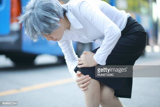 senior woman suffering from knee pain outdoors - one senior woman only stock pictures, royalty-free photos & images