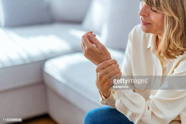 senior woman suffering from pain in hand at home - wrist stock pictures, royalty-free photos & images
