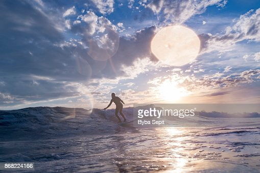 Senior woman surfing a wave