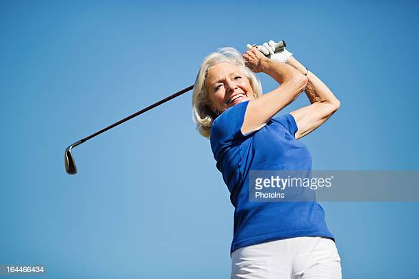 Senior Woman Swinging Golf Club