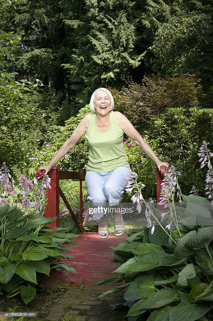 Senior woman swinging on small bridge in garden, laughing : Foto stock